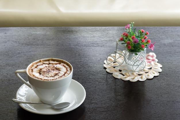 Schönheitsmuster auf spitzenkaffee und ein cupkuchen