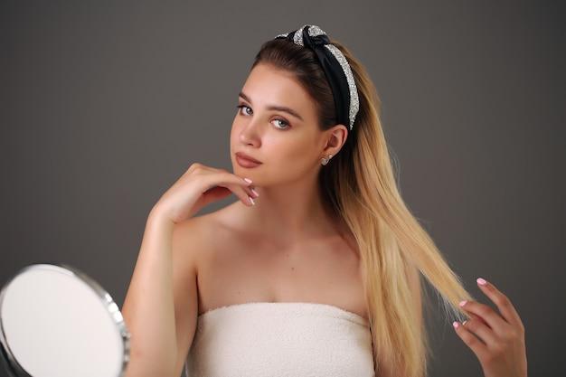 Schönheitsnahaufnahmeporträt der schönen frau auf grau Premium Fotos