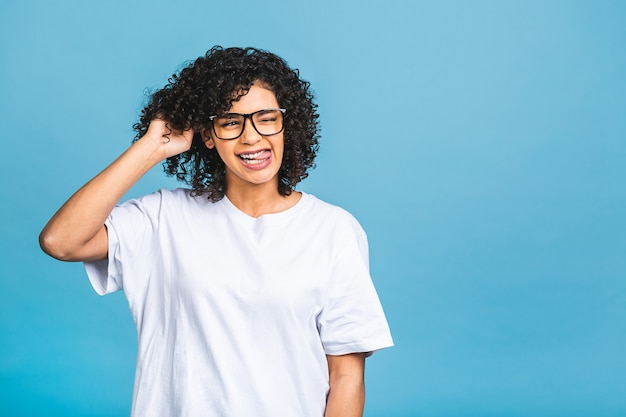 Schönheitsnahaufnahmeporträt des jungen afroamerikanermädchens mit afro-haaren. isoliert über blauem hintergrund.