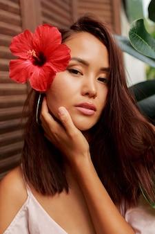 Schönheitsporträt der asiatischen frau mit perfekter haut und hibiskusblume in den haaren, die über holzwand aufwerfen