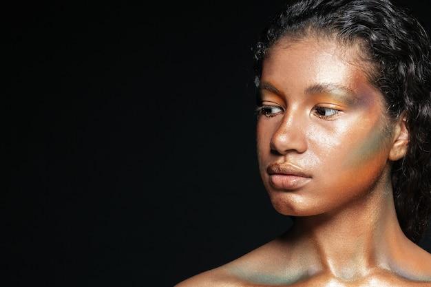 Schönheitsporträt der attraktiven amerikanischen jungen frau mit buntem make-up über schwarzem