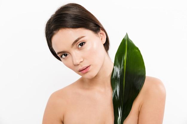 Schönheitsporträt der attraktiven asiatischen frau mit dem braunen haar, das mit grünem blatt aufwirft, lokalisiert über weiß