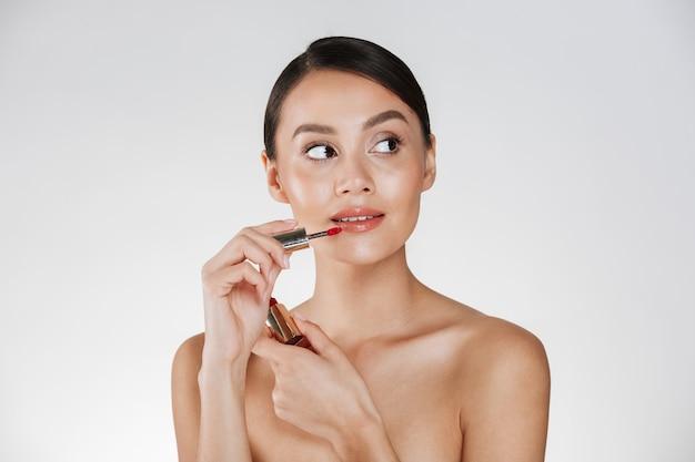 Schönheitsporträt der ausgezeichneten frau mit der gesunden haut, die roten lipgloss auf ihre lippen aufträgt und weg, lokalisiert über weiß schaut