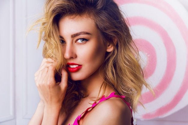 Schönheitsporträt der blonden frau, die im studio über requisiten aufwirft, verzieren.