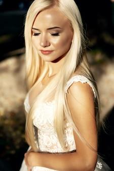 Schönheitsporträt der braut, die modehochzeitskleid mit federn mit luxus-entzückungs-make-up und frisur trägt, studio-innenfoto. junges attraktives multirassisches asiatisches kaukasisches modell. profil von