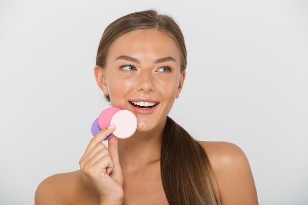 Schönheitsporträt der brünetten hemdlosen frau mit dem langen braunen haar, das lächelnd und bunte kosmetische pads hält, lokalisiert
