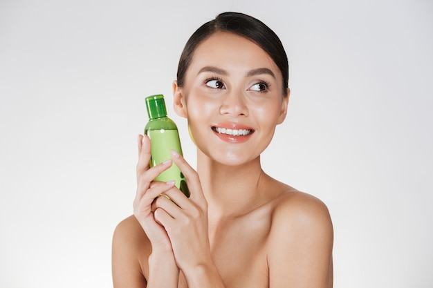 Schönheitsporträt der erfreuten dunkelhaarigen frau mit der sauberen gesunden haut, die lotion für das entfernen von make-up hält und beiseite schaut, lokalisiert über weiß