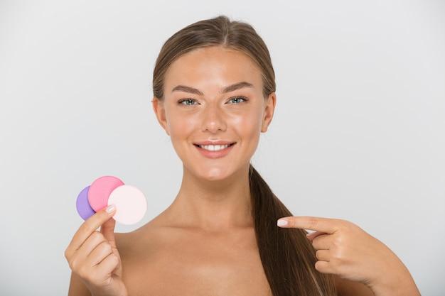 Schönheitsporträt der erfreuten hemdlosen frau mit dem langen braunen haar, das lächelnd und bunte kosmetische pads hält, lokalisiert