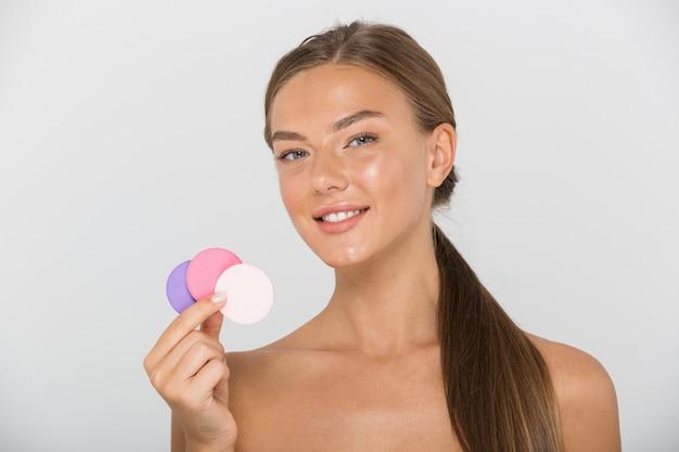 Schönheitsporträt der europäischen hemdlosen frau mit dem langen braunen haar, das lächelnd und bunte kosmetische pads hält, lokalisiert