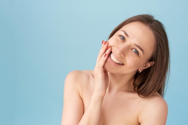 Schönheitsporträt der frau mit sauberer gesunder haut auf blauem hintergrund. lächelnde verträumte schöne frau.