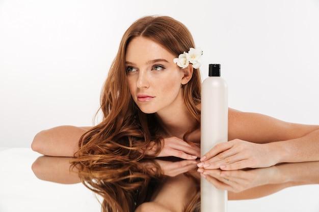 Schönheitsporträt der geheimnisingwerfrau mit blume im haar, das durch die spiegeltabelle mit flasche lotion beim weg schauen sitzt