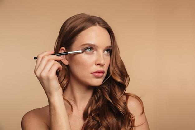 Schönheitsporträt der geheimnisingwerfrau mit dem langen haar, das beim auftragen von kosmetik mit bürste weg schaut