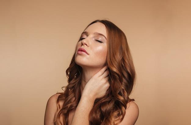 Schönheitsporträt der geheimnisingwerfrau mit dem langen haar, das mit geschlossenen augen beim berühren ihres halses aufwirft