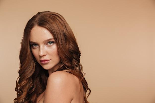 Schönheitsporträt der geheimnisingwerfrau mit dem langen haar, das seitlich aufwirft und schaut
