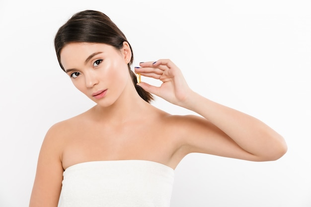 Schönheitsporträt der gesunden asiatischen frau mit dunklem haar, das kapselmedikamente oder vitamin in ihrer hand hält und über weiß aufwirft