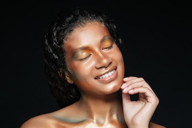 Schönheitsporträt der glücklichen amerikanischen jungen frau mit modemake-up über schwarzem