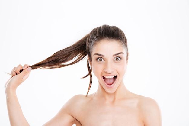 Schönheitsporträt der glücklichen aufgeregten jungen frau, die ihr haar über weißer wand berührt