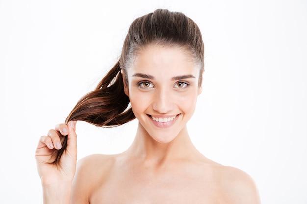 Schönheitsporträt der glücklichen jungen frau, die ihr haar über weißer wand berührt