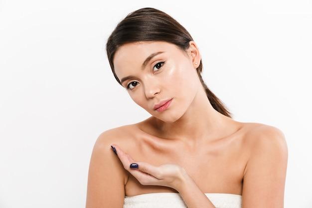 Schönheitsporträt der halbnackten asiatischen frau, die werbeprodukt auf ihrer handfläche hält, lokalisiert über weiß