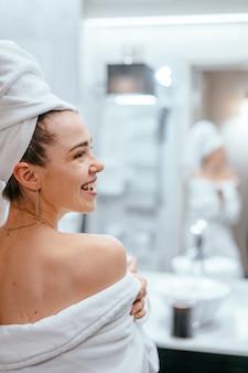 Schönheitsporträt der hübschen frau ein weißes badtuch ankleidend