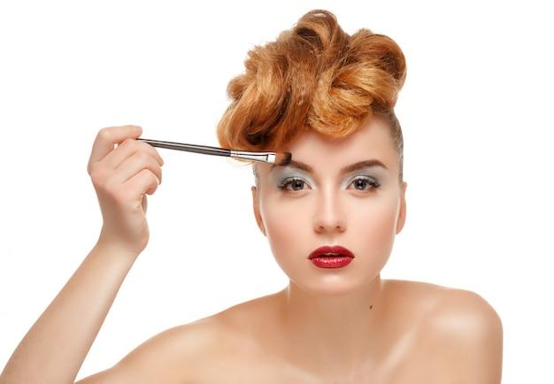 Schönheitsporträt der hübschen frau mit bürste für make-up