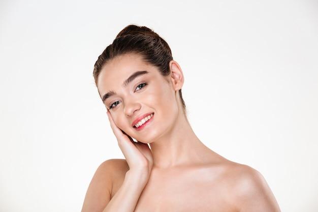 Schönheitsporträt der hübschen halb nackten frau, die braunes haar im brötchen an hand setzt ihr gesicht trägt