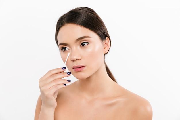 Schönheitsporträt der hübschen hemdlosen frau mit dem brünetten haar, das make-up mit baumwollstab entfernt, lokalisiert über weiß