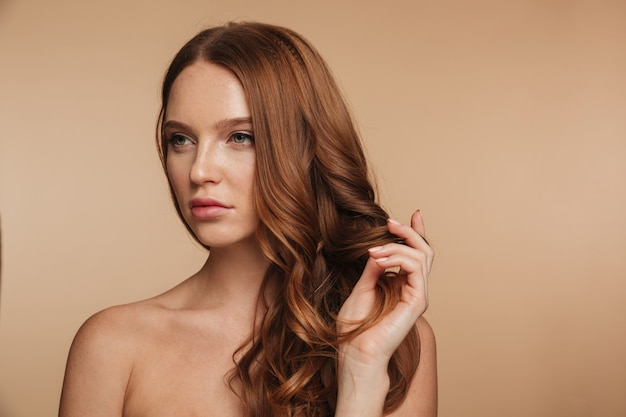 Schönheitsporträt der hübschen ingwerfrau mit dem langen haar, das weg aufwirft und schaut