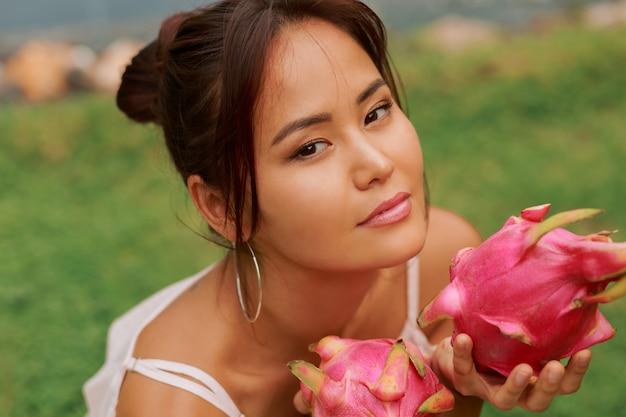 Schönheitsporträt der hübschen jungen asiatischen frau, die pitaya-drachenfrucht hält
