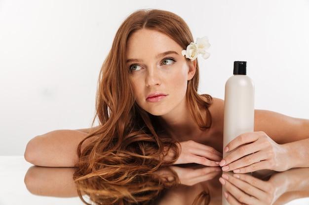 Schönheitsporträt der ingwerfrau mit blume im haar, das durch die spiegeltabelle mit flasche lotion beim weg schauen sitzt