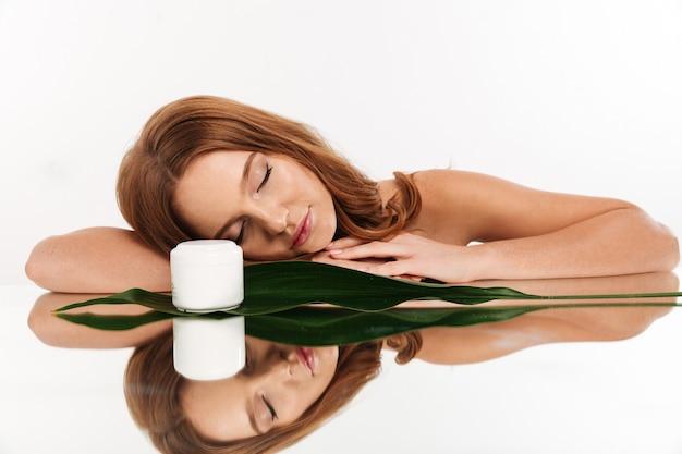 Schönheitsporträt der ingwerfrau mit dem langen haar, das auf spiegeltabelle mit creme für den körper und grünem blatt liegt