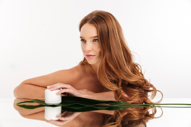 Schönheitsporträt der ingwerfrau mit dem langen haar, das durch die spiegeltabelle mit creme für den körper und grünem blatt beim weg schauen sitzt