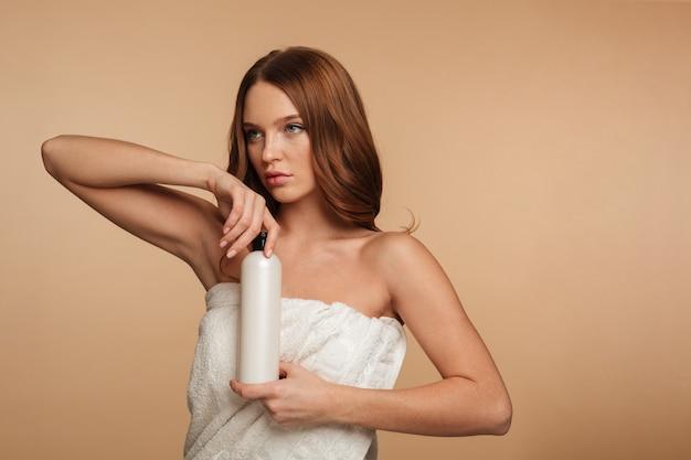 Schönheitsporträt der ingwerfrau mit dem langen haar eingewickelt im tuch, das beim halten der flasche lotion weg schaut