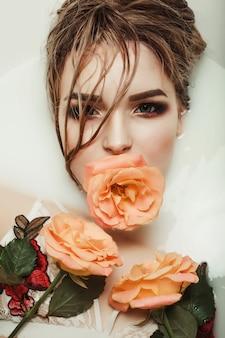 Schönheitsporträt der jungen blonden frau nimmt ein bad mit milch und rosen im mund