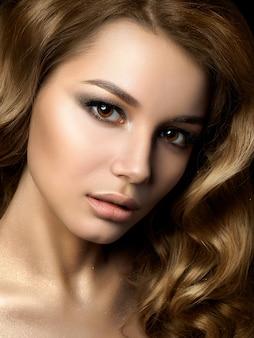 Schönheitsporträt der jungen frau mit goldenem make-up. perfektes haut- und mode-make-up, rauchige augen. sinnlichkeit, leidenschaft, trendiges luxuriöses make-up-konzept.