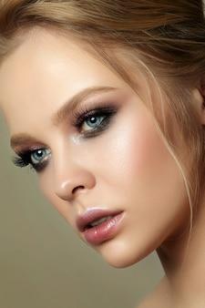 Schönheitsporträt der jungen frau mit klassischem make-up. perfekte haut und buntes make-up für rauchige augen, rauchige augen