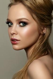Schönheitsporträt der jungen frau mit klassischem make-up. perfekte haut und buntes make-up für rauchige augen