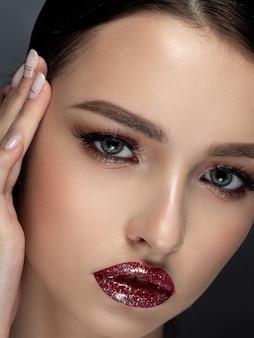 Schönheitsporträt der jungen schönen frau mit glitzernden roten lippen, die ihr gesicht berühren