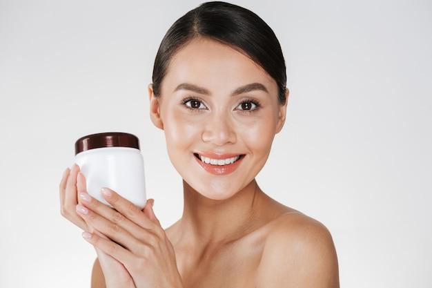 Schönheitsporträt der lächelnden brunettefrau mit der weichen gesunden haut, die bank mit gesichtscreme hält und auf der kamera lokalisiert über weiß schaut