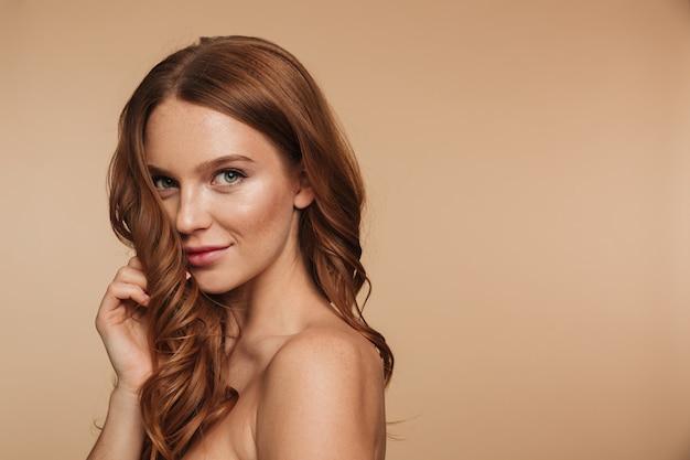 Schönheitsporträt der lächelnden ingwerfrau des geheimnisses mit dem langen haar, das seitlich aufwirft und schaut