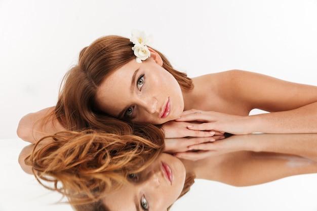 Schönheitsporträt der lächelnden ingwerfrau mit blume im haar, das auf spiegeltabelle beim schauen liegt