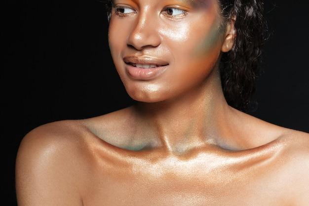 Schönheitsporträt der netten amerikanischen jungen frau mit glänzendem make-up über schwarzem