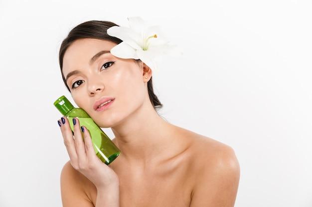 Schönheitsporträt der netten asiatischen frau mit blume in ihrem haar, die körperlotion oder spaöl in der hand hält, lokalisiert über weiß