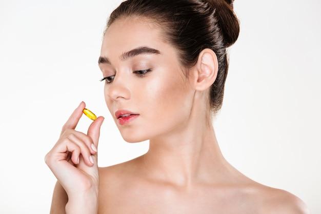 Schönheitsporträt der recht starken frau mit der weichen haut, die pille in ihrer handaufstellung hält