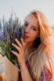 Schönheitsporträt der reizenden blonden frau mit blumenstrauß des lavendels, der kamera betrachtet. perfekte haut. natürliches make-up.