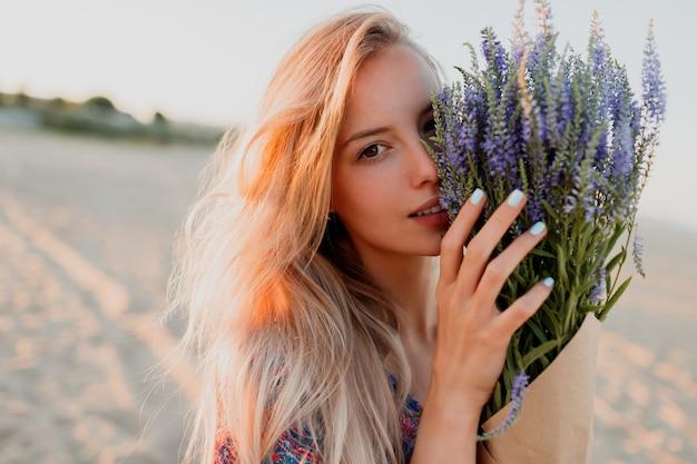 Schönheitsporträt der romantischen blonden frau mit dem blumenstrauß des lavendels, der kamera betrachtet. perfekte haut. natürliches make-up.