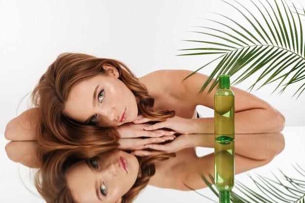 Schönheitsporträt der ruhigen ingwerfrau mit dem langen haar, das auf spiegeltabelle mit flasche lotion beim schauen liegt