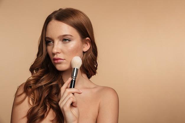 Schönheitsporträt der ruhigen ingwerfrau mit dem langen haar, das beim halten des kosmetikpinsels weg schaut