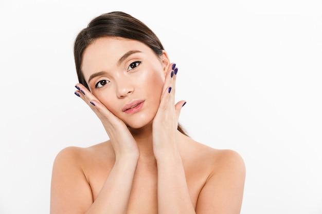 Schönheitsporträt der schönen asiatischen frau mit nagellack, der ihr frisches sauberes gesicht berührt, lokalisiert über weiß