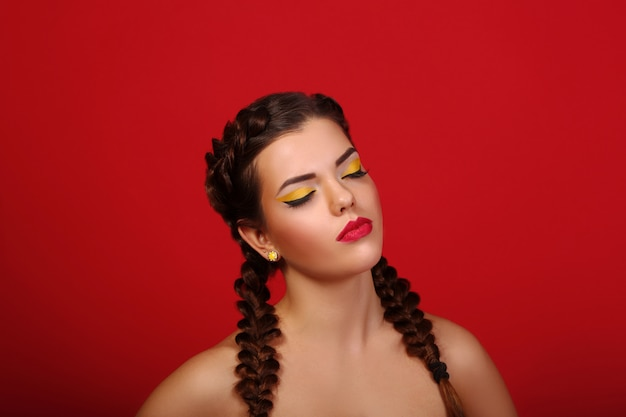 Schönheitsporträt der schönen frauen mit der langen haarbrünette mit den roten lippen und den rauchigen augen mit den geschlossenen augen im studio auf einer roten wand